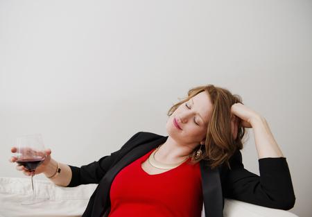 'eyes shut: Woman drinking wine on sofa LANG_EVOIMAGES