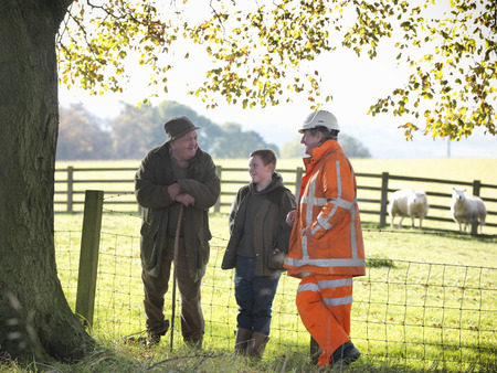 leaning by barrier: Ecologist and farmers talking in field