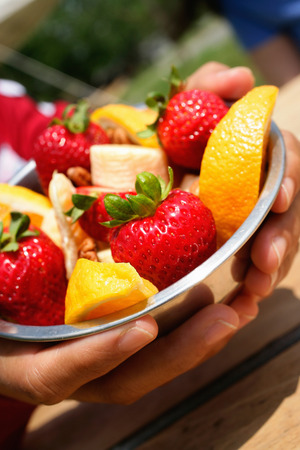 womens hands: Close up of bowl of fruit