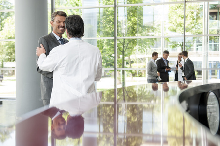 gather: Businessman and doctor shaking hands LANG_EVOIMAGES