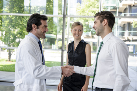 agrees: Doctor and businessman shaking hands