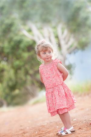 Girl standing on dirt road
