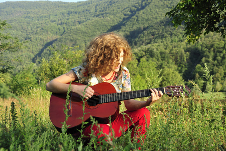 Woman playing guitar in grassy field