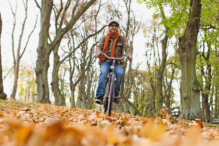 scarves: Man riding bicycle in park