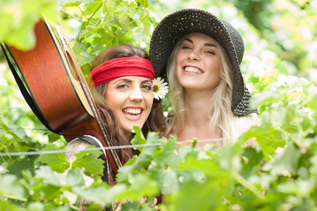 Women holding guitar†in tall plants