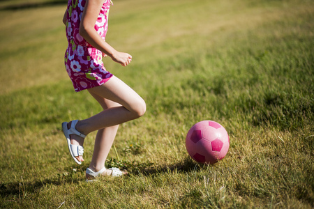 Girl playing soccer in field LANG_EVOIMAGES