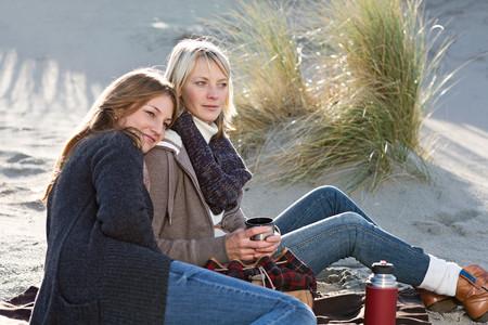 cuddled: Smiling women relaxing on beach