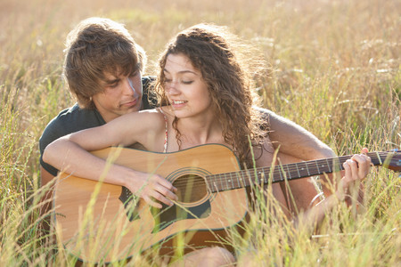 Couple playing guitar in tall grass