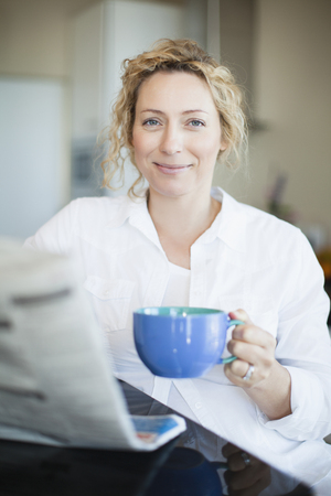 mornings: Woman drinking coffee and reading paper LANG_EVOIMAGES