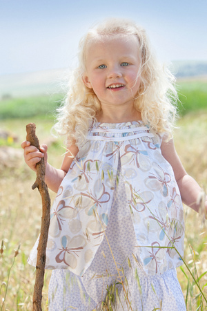 joyous: Toddler girl standing in tall grass LANG_EVOIMAGES