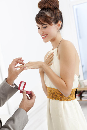 enquiring: Man putting engagement ring on fiance