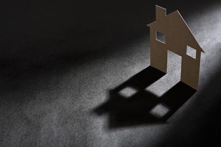 genesis: Cardboard house shape casting shadow