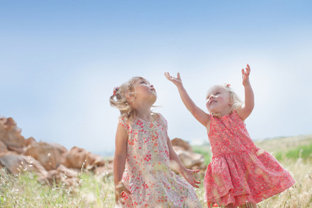 Girls playing in tall grass outdoors LANG_EVOIMAGES