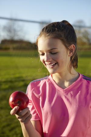 Girl eating apple in field