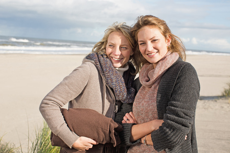 posed: Smiling women standing on beach