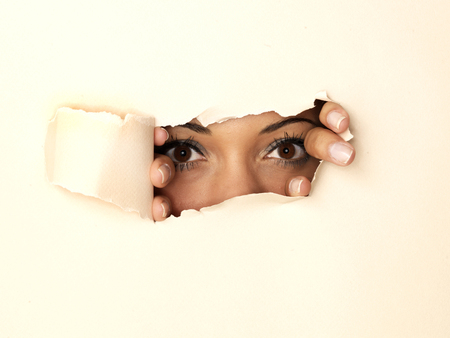 Woman peeking through hole in wall LANG_EVOIMAGES