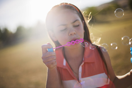 Girl blowing bubbles outdoors LANG_EVOIMAGES