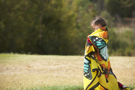 Girl wrapped in colorful towel outdoors LANG_EVOIMAGES