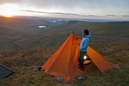 brecon beacons: Hiker at campsite overlooking landscape