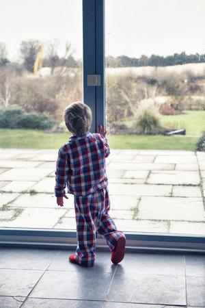 genesis: Boy in pajamas looking out window