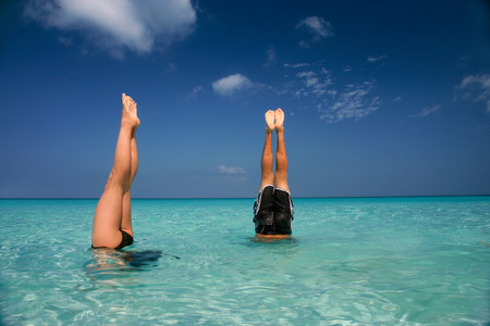 People in headstands in tropical water LANG_EVOIMAGES