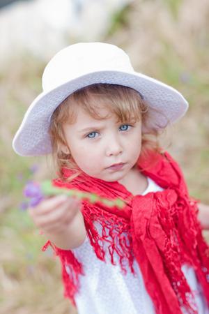 provide: Girl holding flower in field