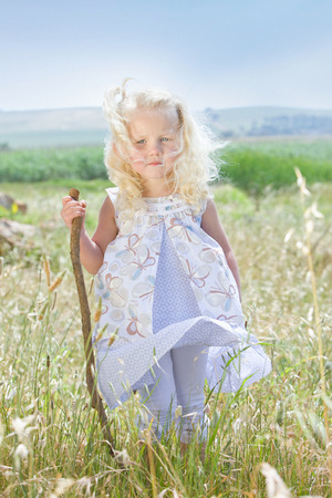 wind blown hair: Toddler girl standing in tall grass LANG_EVOIMAGES