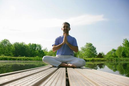 pleading: Man meditating on wooden pier