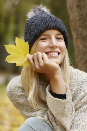 Woman holding autumn leaf outdoors