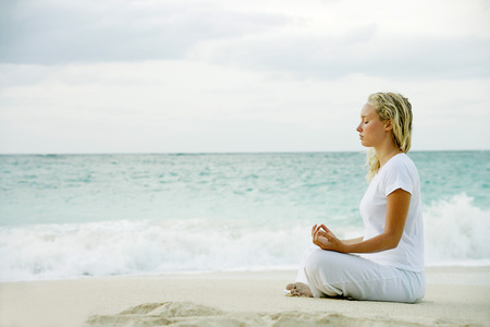 spiritual beings: Woman meditating on tropical beach