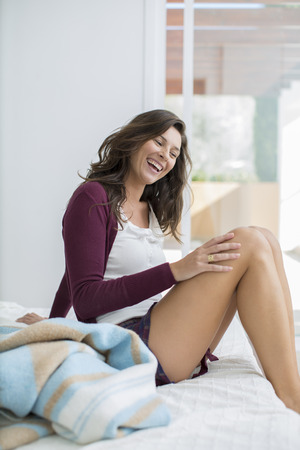 enthusiastically: Smiling woman sitting on bed LANG_EVOIMAGES