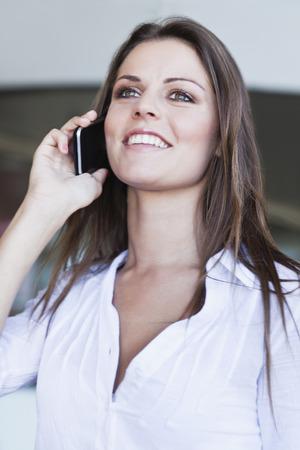 通信: Woman talking on cell phone outdoors