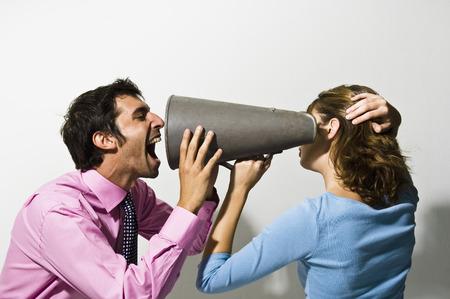 facing backwards: Businessman shouting into colleagues ear