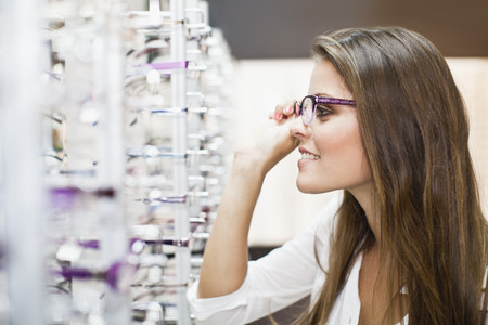 decide deciding: Woman trying on glasses in store