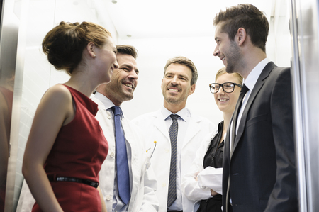 shared sharing: Doctors and business people in elevator