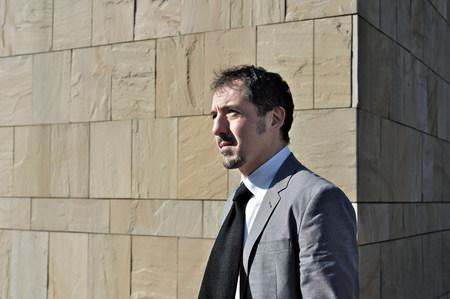 通信: Mature businessman standing by brick wall outdoors