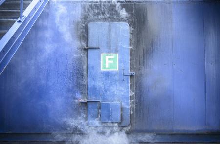 seeps: Smoke pouring from behind steel door LANG_EVOIMAGES