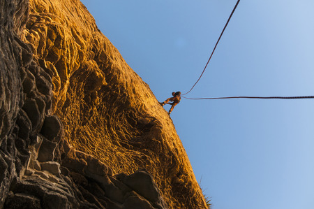Rock climber scaling steep rock face LANG_EVOIMAGES