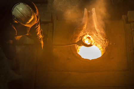 Worker stirring molten metal in foundry