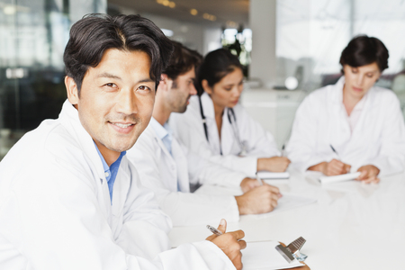 Doctor smiling in meeting LANG_EVOIMAGES