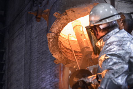 industrialization: Worker cleaning metal flask in foundry