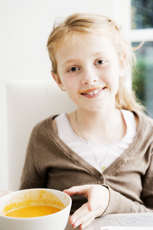 Smiling girl holding bowl of soup