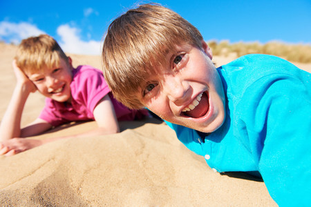 Two blonde haired boys lying on beach LANG_EVOIMAGES