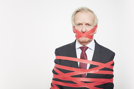 Businessman wrapped in red tape LANG_EVOIMAGES
