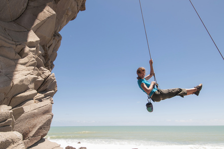 Rock climber abseiling jagged cliff LANG_EVOIMAGES