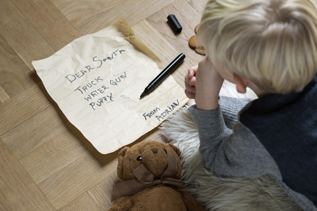 somber: Boy writing Christmas list for Santa