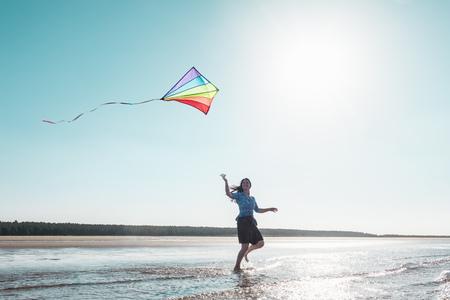 sun energy: Woman flying kite on beach