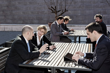Business people working at outdoor tables