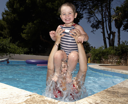 arms lifted up: Mother and daughter in swimming pool