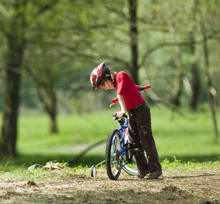 Boy climbing on bicycle in park